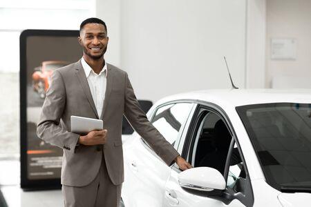 Venta de coches. Vendedor negro vendiendo y mostrando coche nuevo de pie en el centro de concesionarios de lujo. Enfoque selectivo, espacio vacío