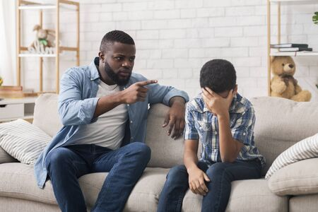 Angry black father scolding stubborn little son for bad behavior at home, boy making facepalm gesture, free space Imagens