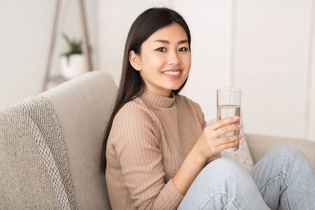 Stay hydrated. Asian girl holding glass with clean mineral water, sitting on sofa, free space