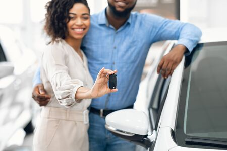 Happy Black Couple Showing New Auto Key Embracing Standing In Dealership Store. Cropped, Shallow Depth