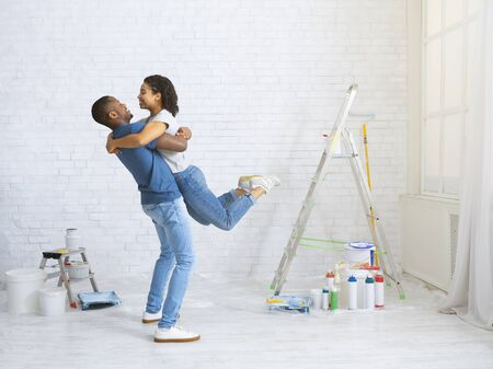 Afro american couple in love hugs on background of home renovation, free space