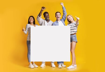 Multiracial group of positive teenagers standing together in row and displaying white empty placard, yellow studio background