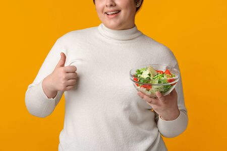 Organic Nutrition Concept. Unrecognizable Plump Woman Holding Fresh Vitamin Vegetable Salad And Gesturing Thumb Up, Yellow Background, Cropped