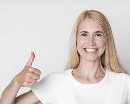 Approval Concept. Smiling middle-aged woman showing thumbs up gesture isolated over gray studio wall, copyspace