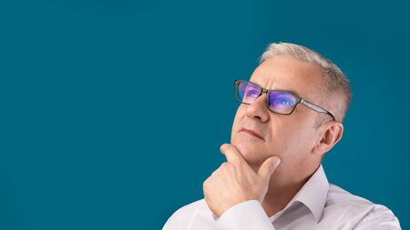 Making Decision. Close up portrait of pensive mature man in specs looking at copy space isolated over blue studio wall Standard-Bild