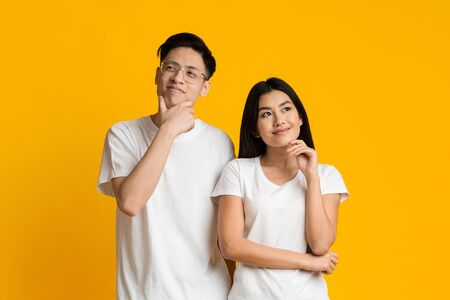 Planning future together. Young asian couple day dreaming on yellow studio background Reklamní fotografie