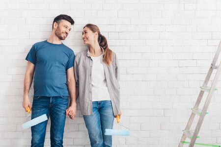 Smiling couple in love painting their new home or flat, happy together holding paint rollers and looking at each other