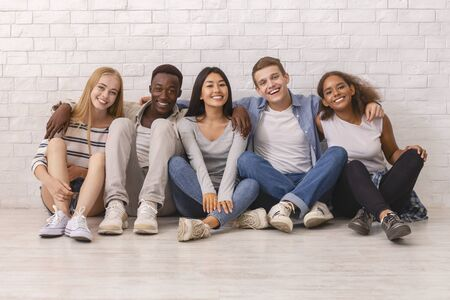 Multiracial happy students posing over white brick wall, sitting on floor and embracing, friendship concept Foto de archivo