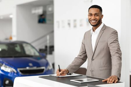 Car Sales Manager Working Selling Automobiles Standing At Desk In Luxury Dealership Office. Selective Focus, Copy Space