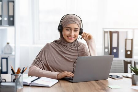 Foreign Languages Online Concept. Portrait Of Smiling Arabic Girl In Hijab And Headset Watching Webinar On Laptop While Sitting In Office Standard-Bild