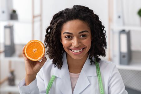 Close up portrait of female doctor cheerful afro woman holding orange half, recommending frresh fruits to eat