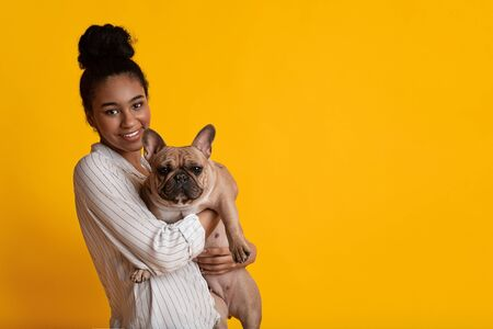 Love between dog and owner. Happy afro girl hugging her french bulldog puppy and smiling at camera over yellow studio background with copy space