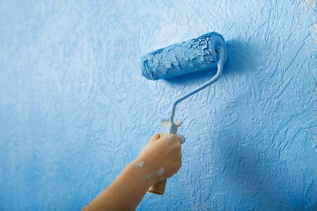 Homemade home repair. Female hand painting wall with roller in blue color