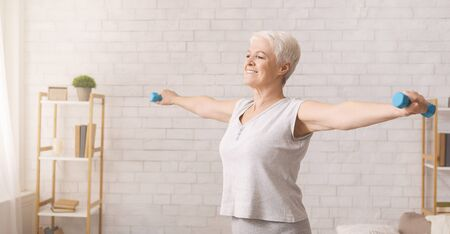 Active senior woman doing morning work-out exercises with dumbbells at home, panorama, free space