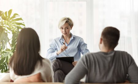 Professional Help. Family Counselor Giving Advice To Married Couple How To Improve Relationship Sitting In Office. Back View, Selective Focus