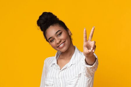 Young african american woman showing peace, victory or number two gesture with fingers, posing over yellow background in studio, free space