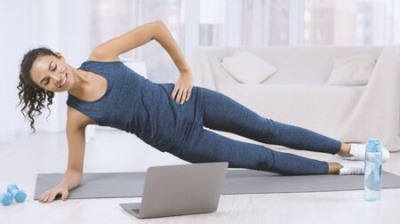 Happy Latin woman doing side plank exercise while watching workout video on laptop at home 스톡 콘텐츠