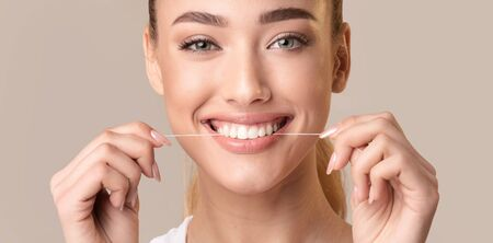Teeth Flossing. Smiling Woman Using Tooth Floss Cleaning And Caring For Perfect White Teeth Posing Over Beige Background. Panorama
