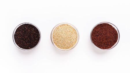 Black, red and white quinoa In glass cups on white background, panorama