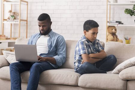 Afro dad busy with laptop, working online at home, sad bored offended son sitting nearby, free space