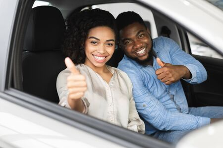 Great Car. Happy Afro Couple Gesturing Thumbs Up Sitting In New Auto Buying Automobile In Dealership Store. Selective Focus