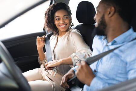 Car Owners. Joyful Black Spouses Putting On Seat Belts Sitting In New Luxury Automobile In Dealership Store. Selective Focus