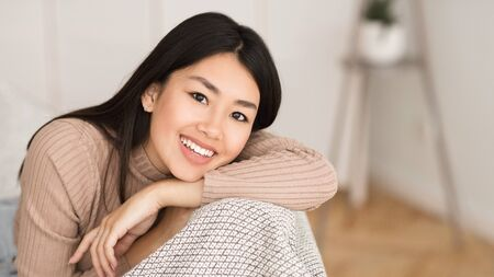 Pretty asian girl relaxing at home, smiling to camera in living room, panorama with copy space Foto de archivo - 141062858
