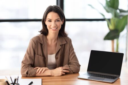 Web Designer. Beautiful woman sitting at desk by laptop with blank screen, looking at camera, copyspace, mock up