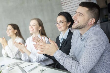 Professional education. Happy business listeners clapping hands at business meeting