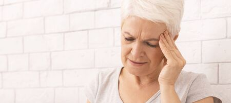 Age migraine. Senior woman suffering from headache, panorama, free space