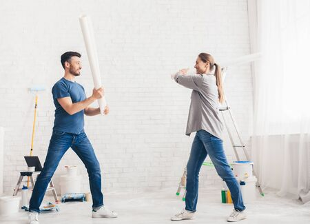 Happy young couple fighting with rollers and smiling each other while having break during repairment, white bricks wall Stock Photo