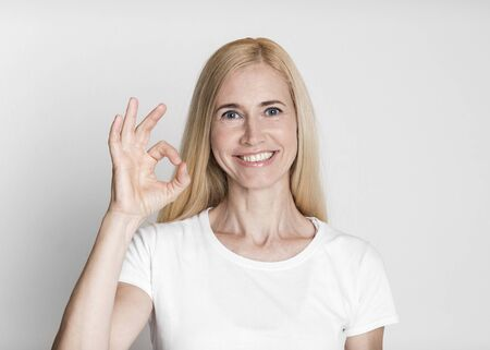 Im Fine. Happy middle-aged woman showing approval gesture, smiling isolated over gray studio wall, copyspace
