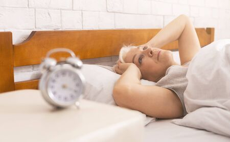 Sleep disorder in old age. Senior woman suffering from headache, lying in bed early in morning