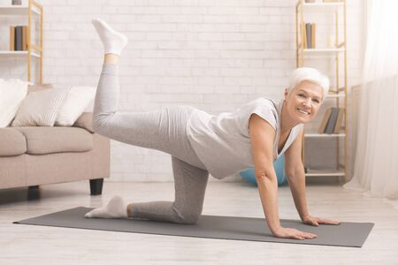 Senior fitness lady standing on all fours, straightening leg up, exercising at home