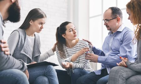 Concerned support group mebers comforting emotional young woman at therapy session, offering glass of water, panorama Stock Photo