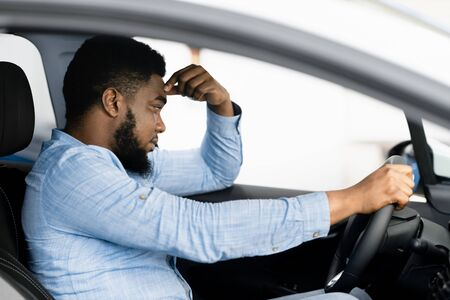 Depressed African Man Sitting In Drivers Seat Of New Too Expensive Car, Thinking Of Money Problems In Auto Dealership Store