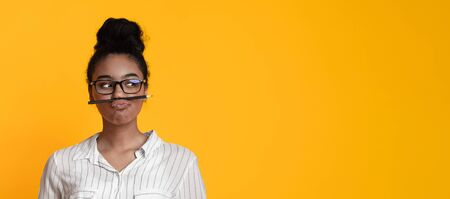 Black girl in glasses keeping pencil like mustache and looking aside, fooling, having fun while posing on yellow background, panorama with free space