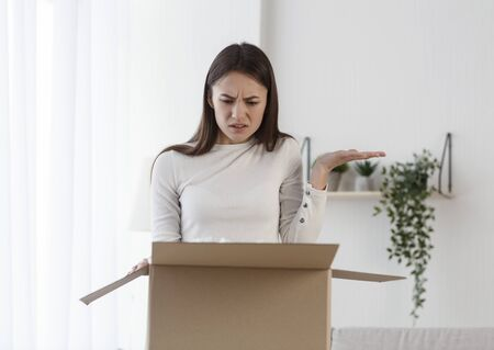 Disappointed woman receive damaged wrong parcel, girl unpacking cardboard delivery package