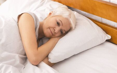 Loneliness in old age. Upset senior woman thinking about life in bed, free space