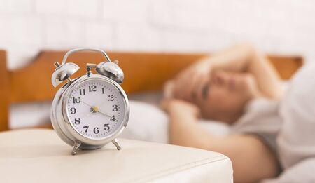 Insomnia problem. Senior woman lying in bed, woke up at 4 am, focus on alarm clock, panorama