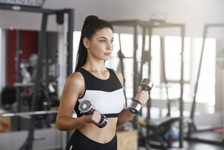Fitness and workout. Pretty young woman using dumbbells in gym Standard-Bild