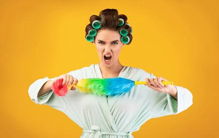 Furious Housewife Shouting Holding Cleaning Brush Feather Duster Standing On Yellow Studio Background. Household And Domestic Chores
