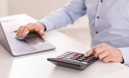 Payroll Concept. Close up of middle-aged accountant using calculator and computer, selective focus