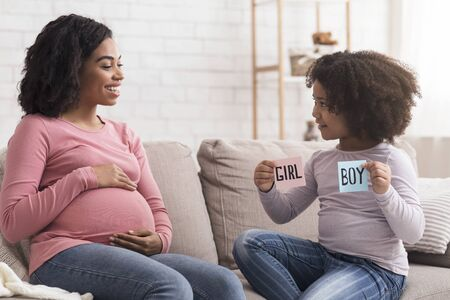 Little black girl holding pink and blue cards next to her pregnant mom, guessing baby gender together, sitting on couch at home