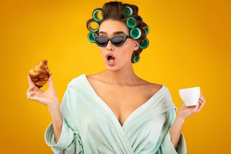Glamorous Housewife. Attractive Woman With Curlers Having Coffee And Croissants Wearing Dressing Gown And Sunglasses Posing On Yellow Studio Background. Stock fotó
