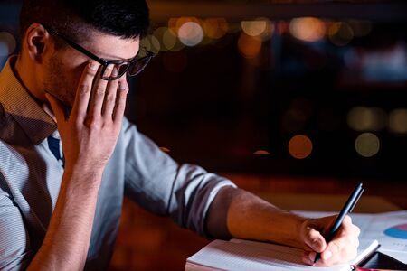 Eyestrain. Businessman Touching Aching Eye Under Glasses Working Taking Notes Sitting In Office At Night.