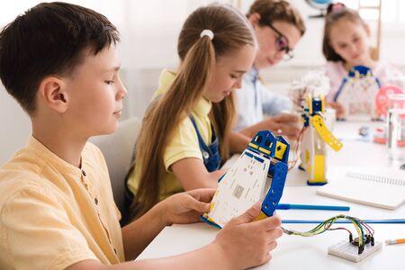 Educación de tallo. Niño de escuela trabajando en un proyecto, haciendo un robot de bricolaje con compañeros de clase en el fondo