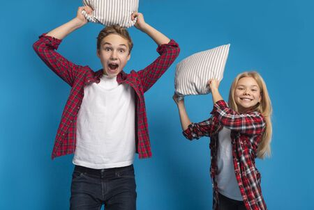 Playful Little Boy And Girl Fighting With Pillows At Camera, Standing Over Blue Background In Studio, Free Space
