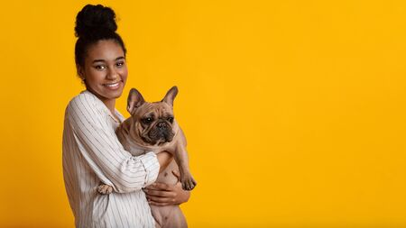Love for Pets. Portrait Of Happy Black Girl With Cute French Bulldog Dog Puppy In Hands Posing Together Over Yellow Background, Panorama, Free Space