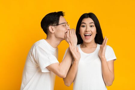 Asian man sharing secret or whispering gossips into his girlfriends ear, yellow studio background